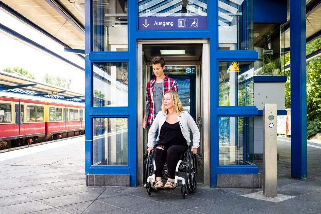 Photo of a woman in a wheelchair, accompanied by a man, leaving an elevator at the suburban railroad.
