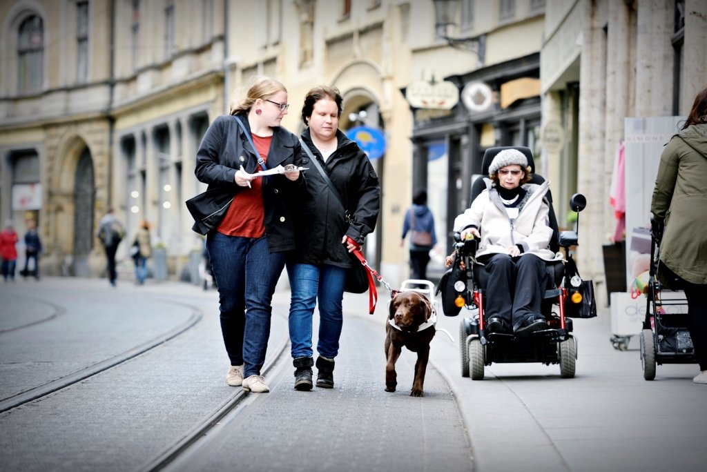 Photo of a blind woman with assistance dog and a woman in a wheelchair in a city center