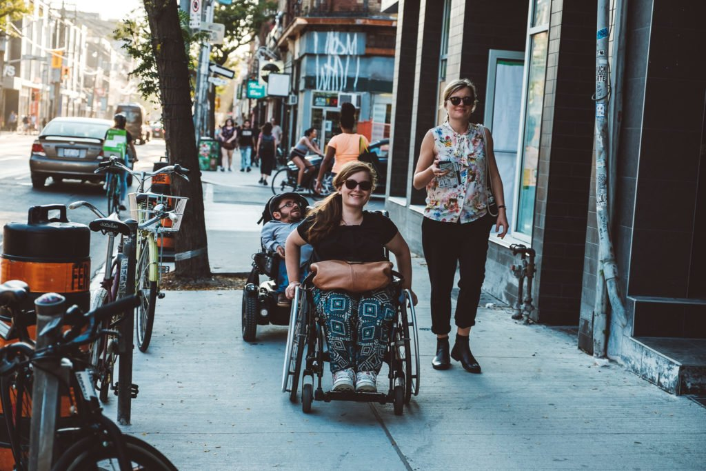 Two wheelchair users and a pedestrian are walking down the street.