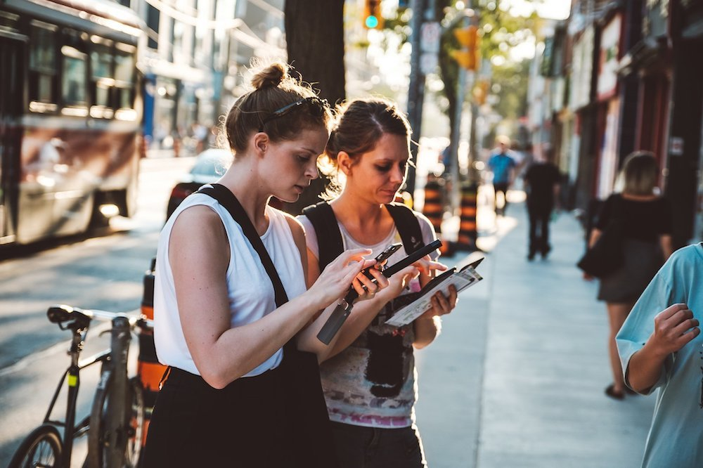 Two women are standing on a sidewalk typing away on their smartphones.