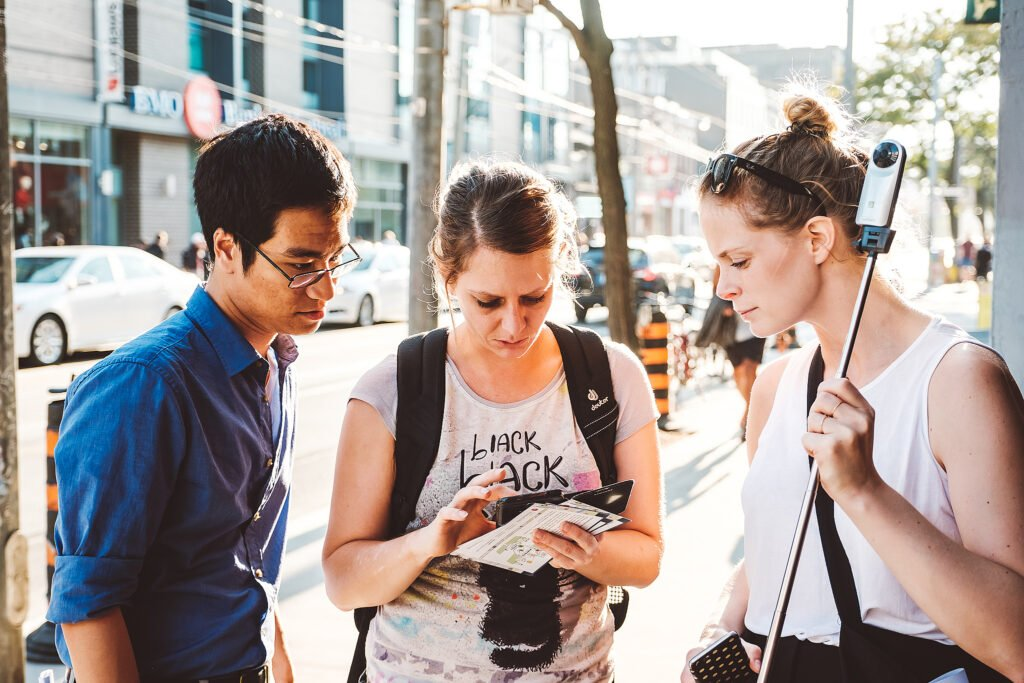 Three people participating in a mapping event. They are looking at a smartphone together. Atmosphare is very summery and urban.