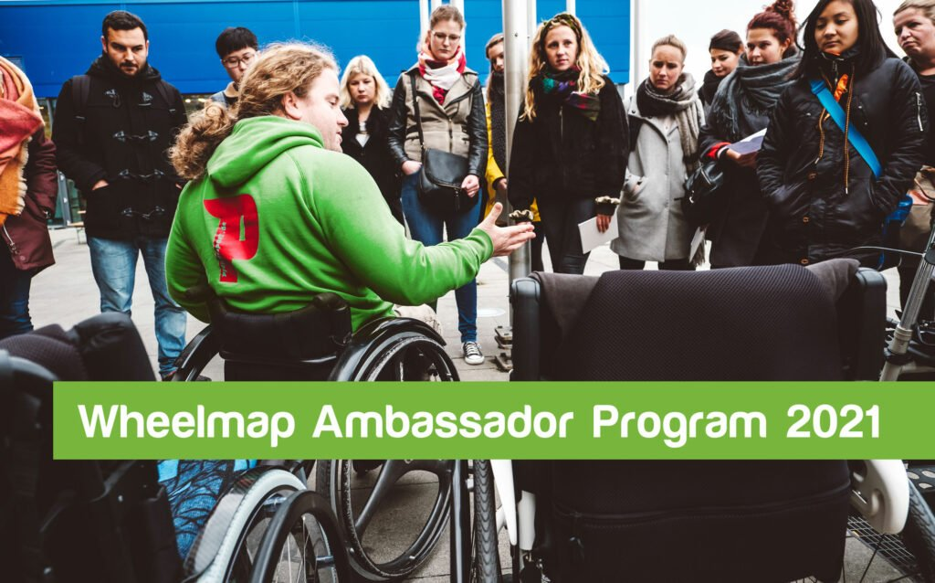 A person sitting in a wheelchair explains something to bystanders. Text: Wheelmap Ambassador Program 2021