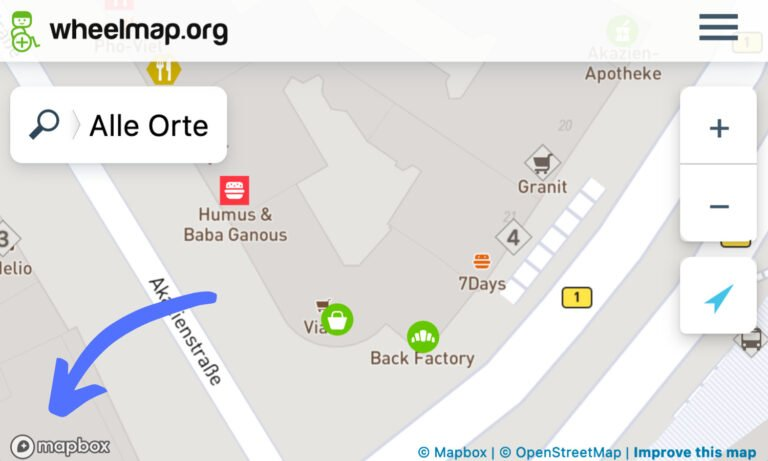 Screenshot of Wheelmap.org. An arrow points to the mapbox logo in the bottom left.