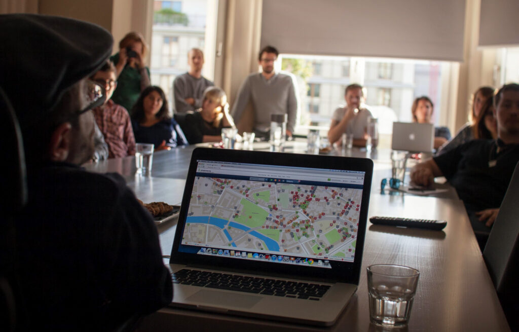 Photo: People in a conference room. A Laptop on the Tabel shows Wheelmap.org