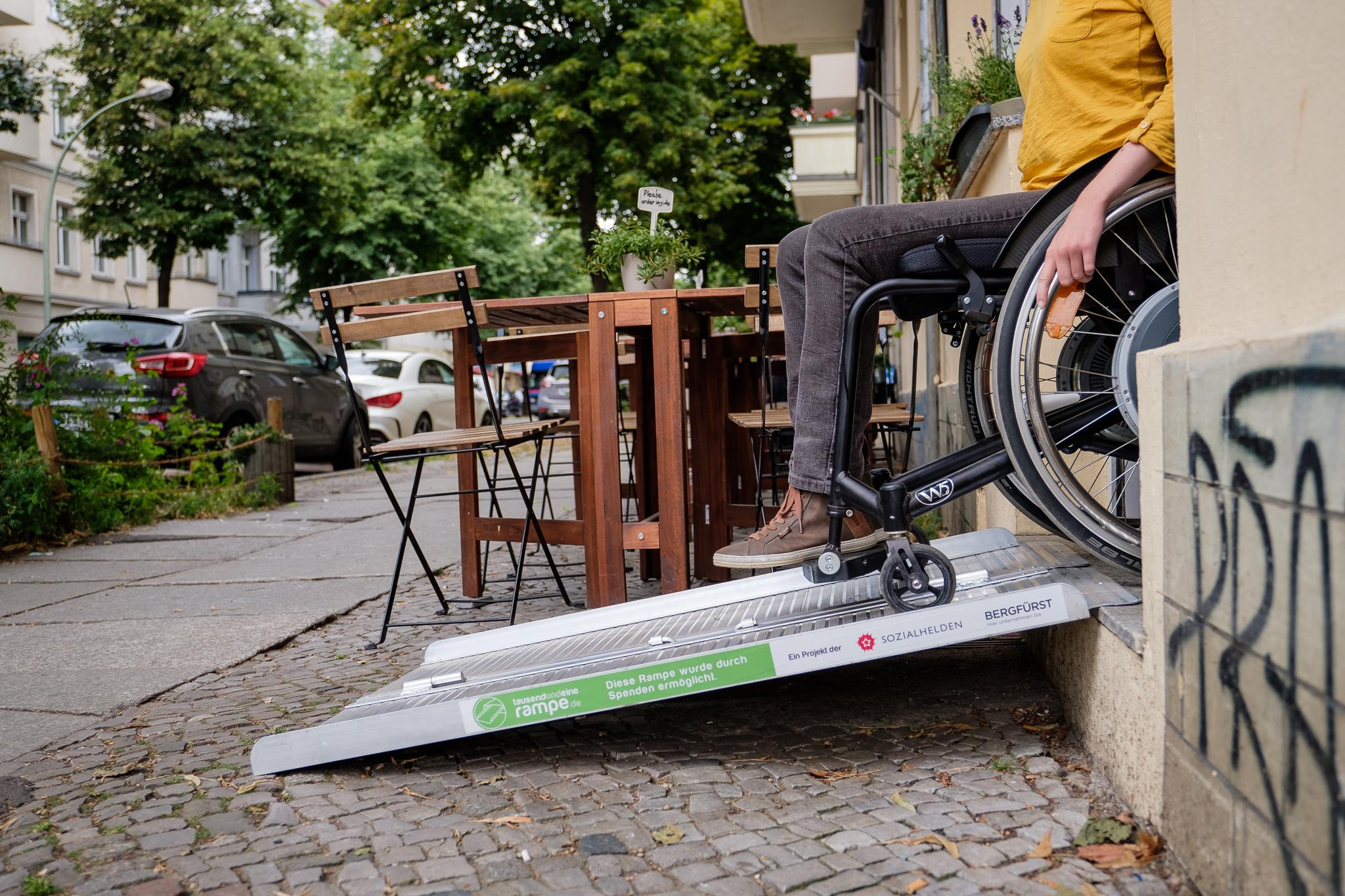 Frau mit Rollstuhl nutzt eine mobile Rampe