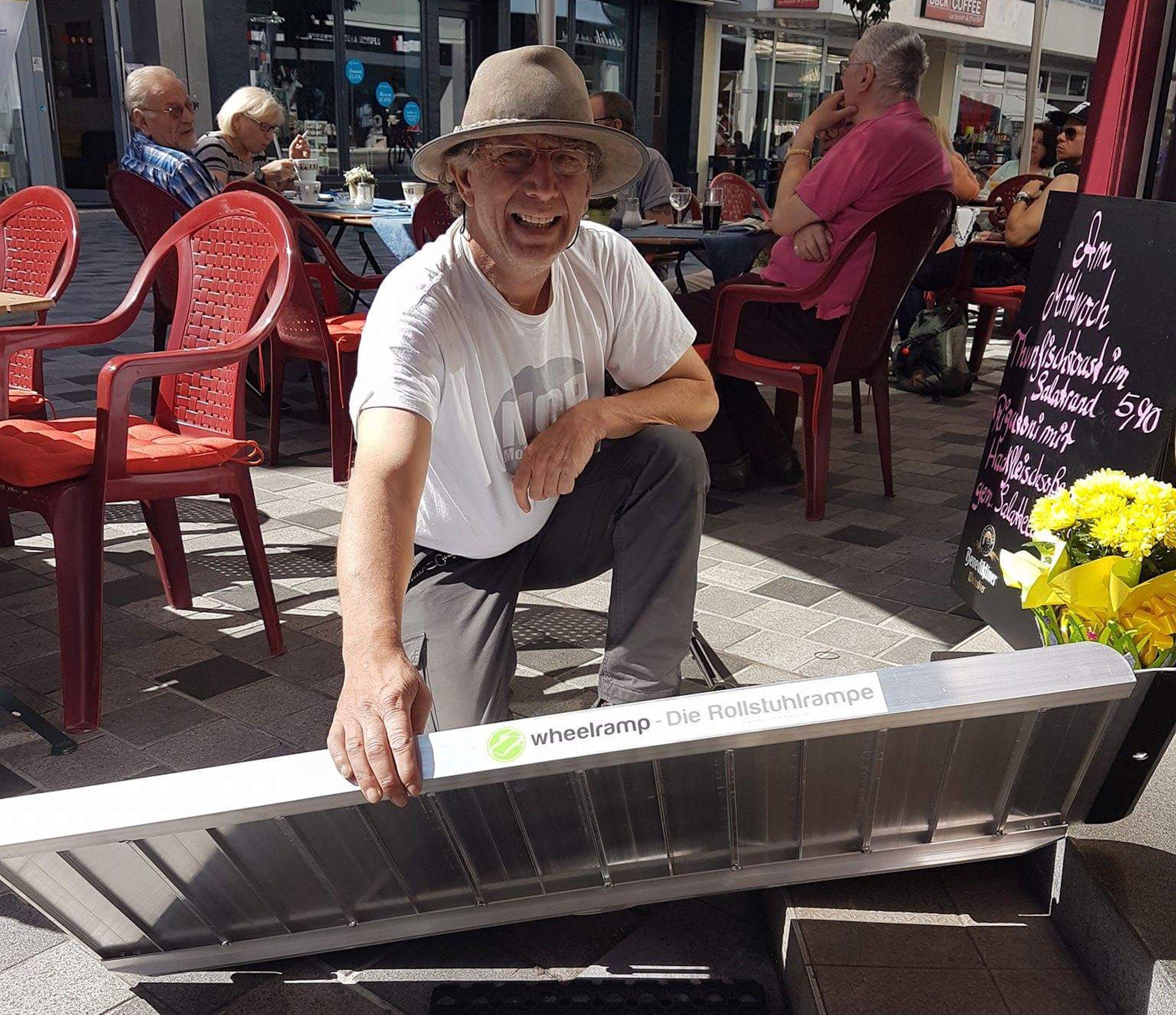 """Winfried Hoffmann legt in der Stadt eine mobile Rampe mit der Aufschrift """"Wheelramp"""" an eine zweistufige Treppe. Im Hintergrund sitzen Menschen im Café auf roten Plastikstühlen."""