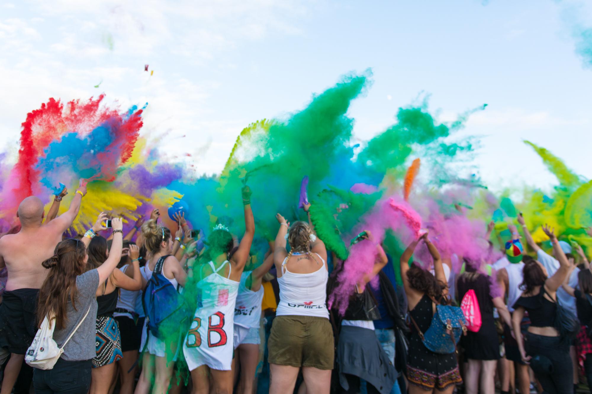 Menschen werfen auf der sogenannten Color Party bunte Farben in die Luft