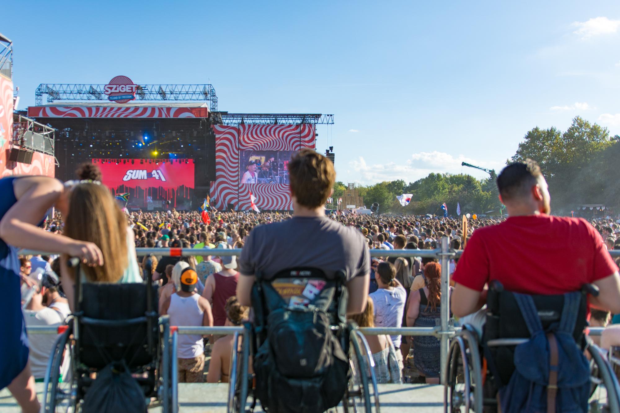 """Rollstuhlfahrer auf einem Podest blicken über die Menschenmenge auf die Bühne, auf der """"Sum 41"""" spielen"""
