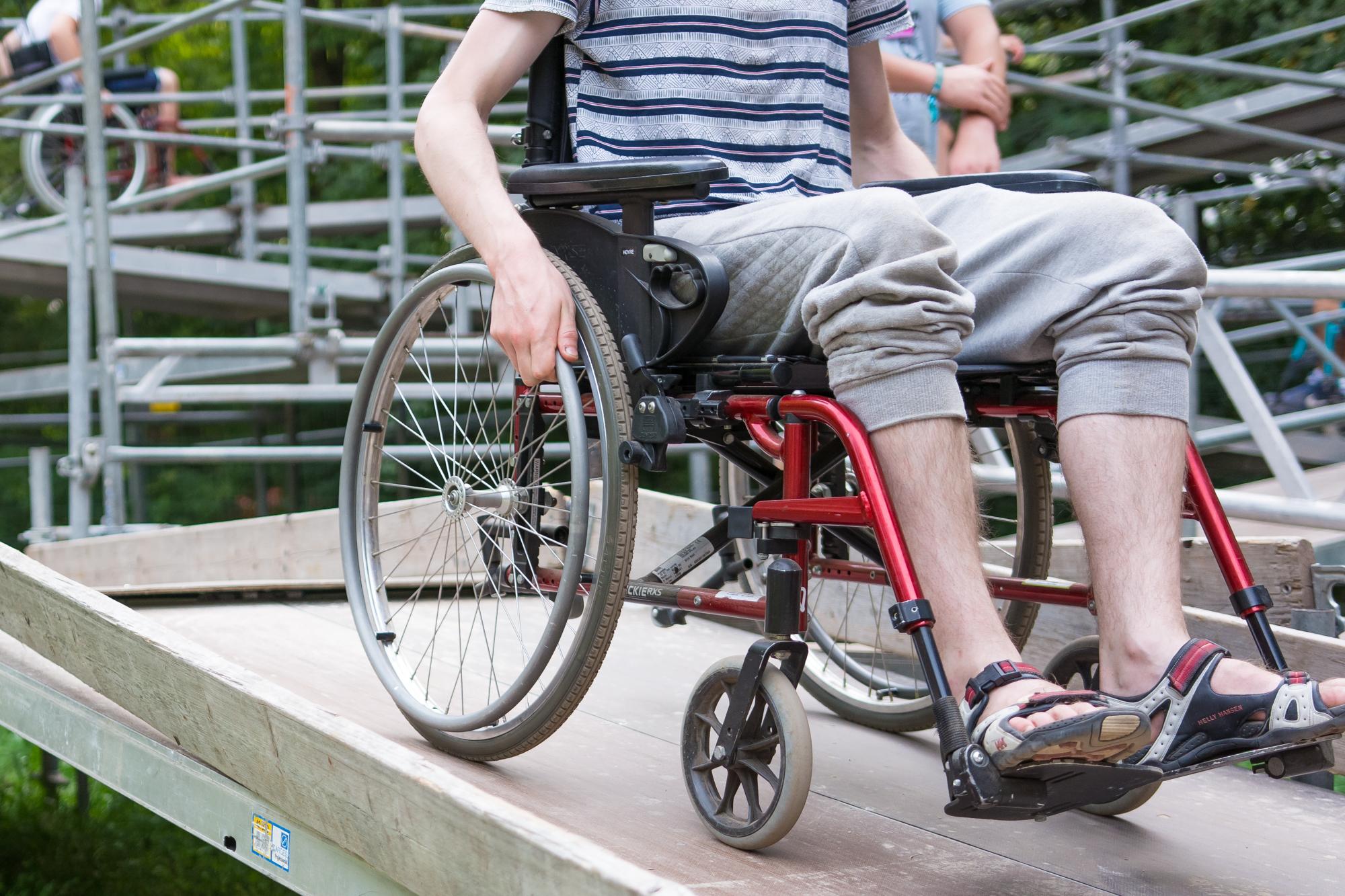 Angeschnittenes Bild eines Rollstuhlfahrers auf einer schrägen Plattform