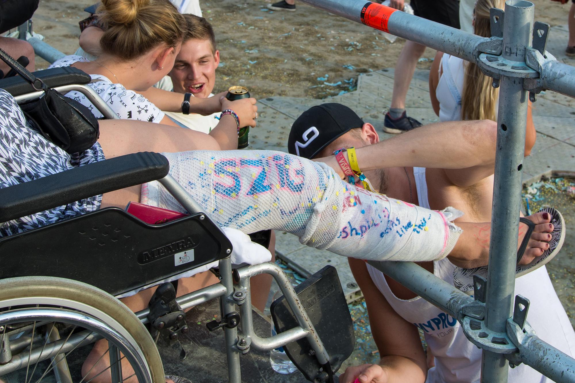 Unterschreiben auf dem eingegipsten Bein eines Mädchens im Rollstuhl