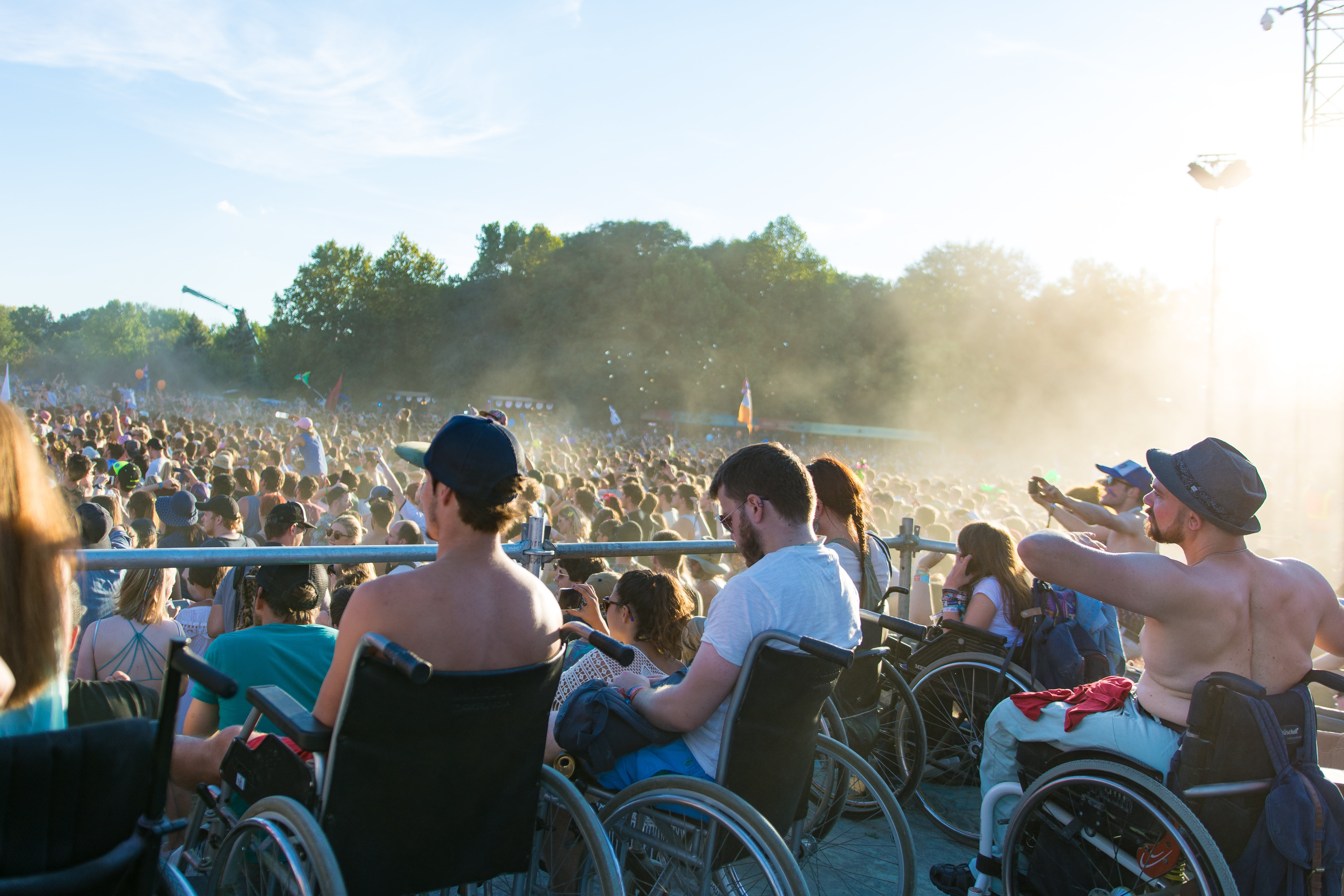 Wheelchair users and the festival crowd looking in the direction of the main stage.