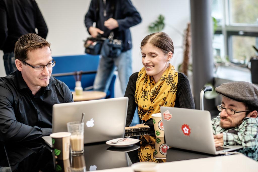 Drei Personen sitzen um eine Tisch herum. Sie arbeiten an Laptops, auf dem Tische steht Kaffe