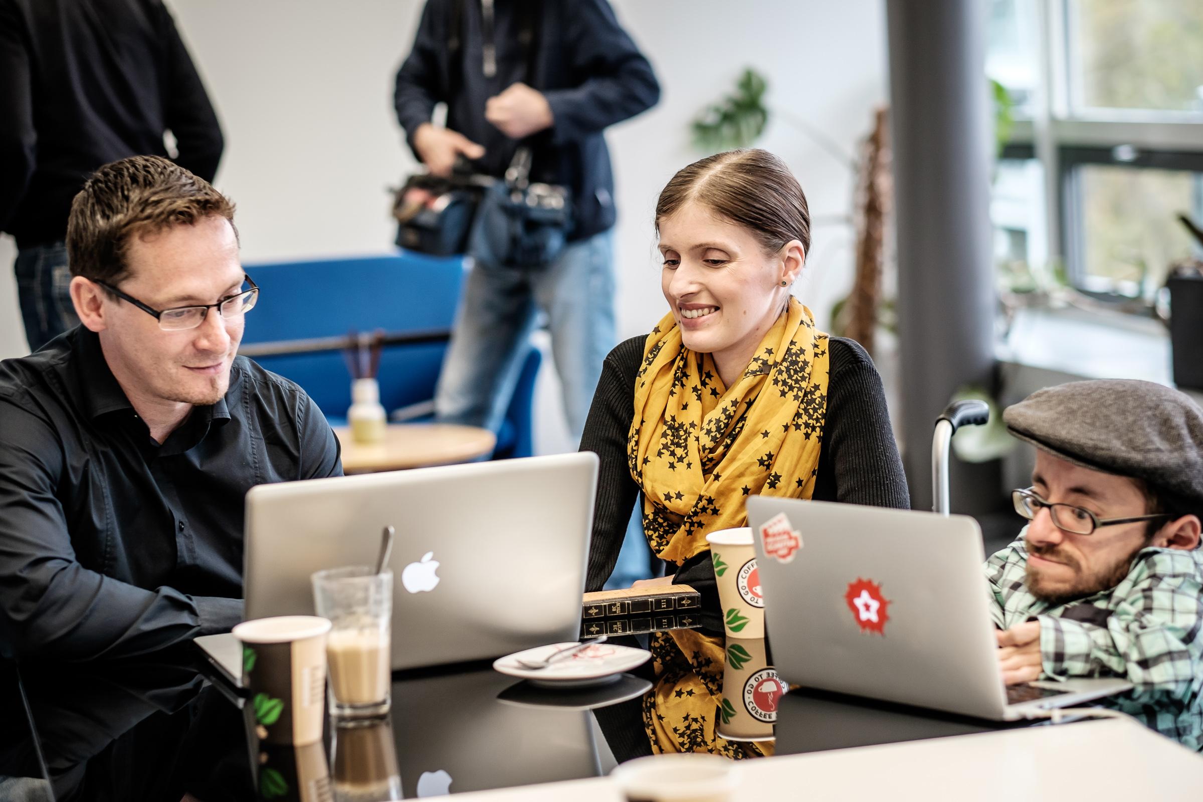 Drei Personen sitzen für die IT-Entwicklung der Wheelmap mit Kaffee am Tisch zusammen und schauen auf die Bildschirme der MacBooks. Die Frau in der Mitte und der kleinwüchsiger Mann links sind im Rollstuhl.