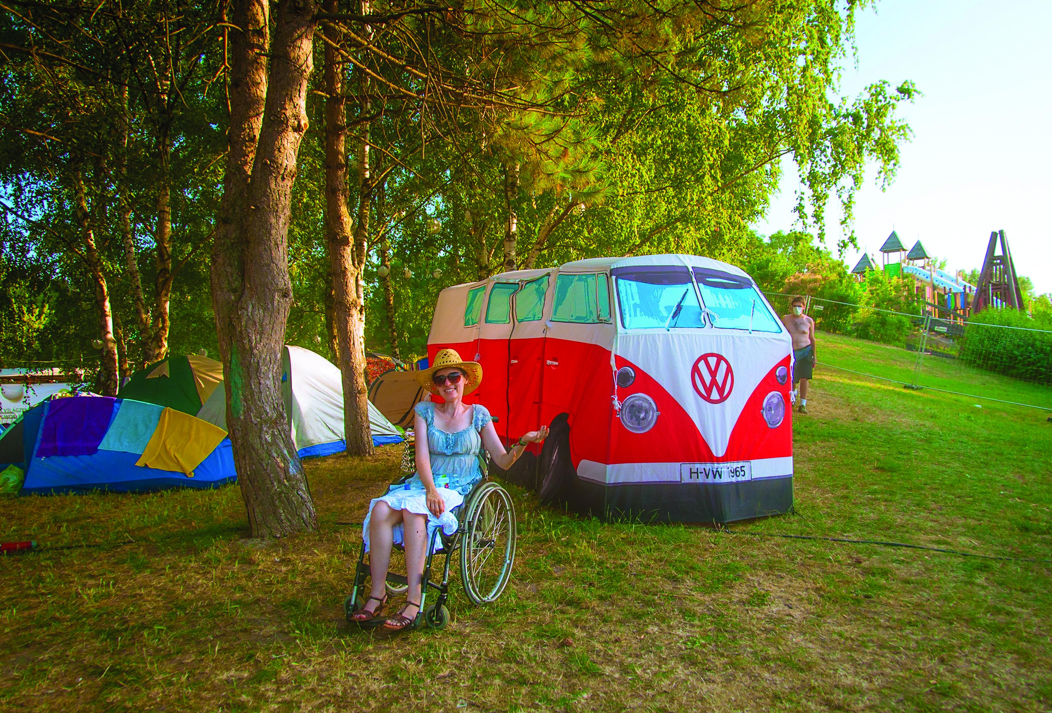 Eine Frau mit Rollstuhl steht vor dem Zelt, das aussieht wie ein VW-Bus.