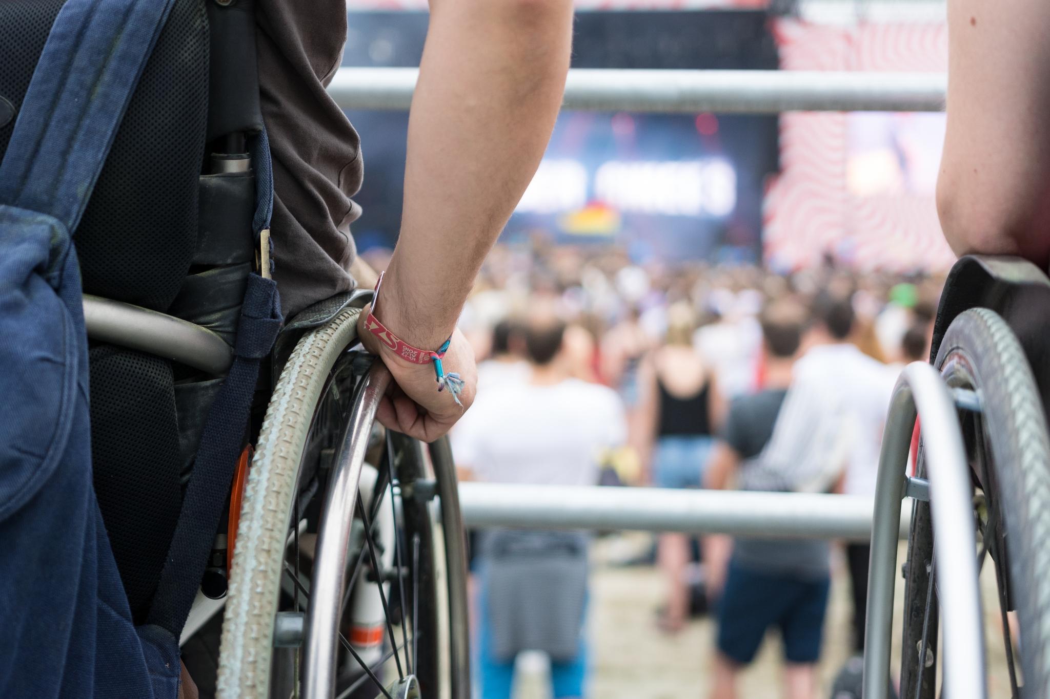 Zwei Rollstuhlfahrer*innen stehen auf der Tribüne für Rollstuhlfahrer. Vor ihnen sieht man verschwommen die Festivalbühne.