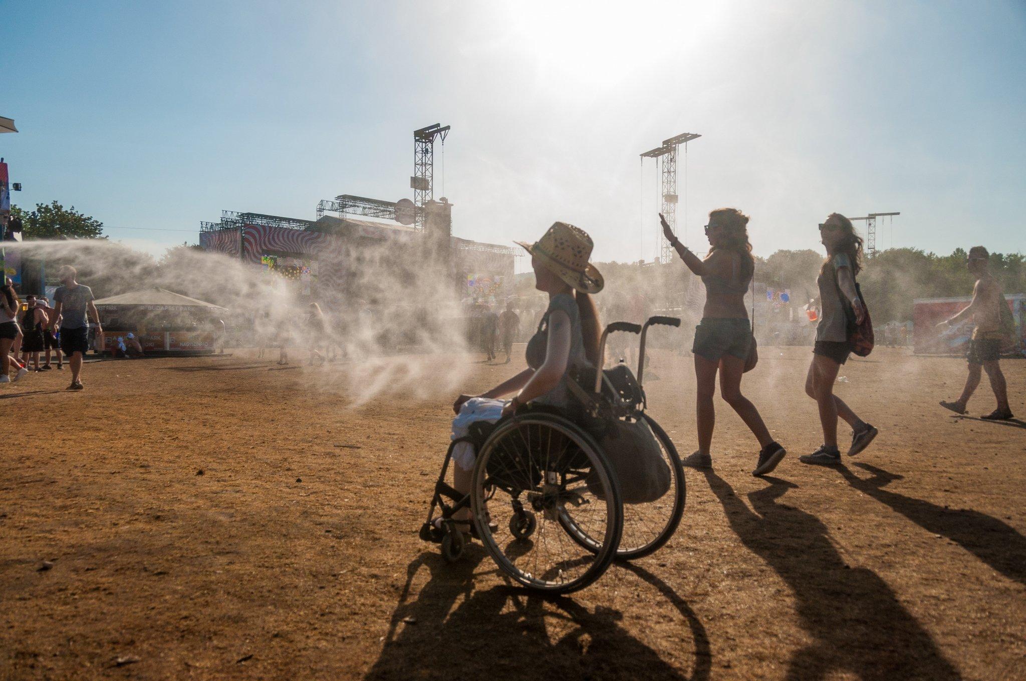 Rollstuhlfahrerin Adina auf dem sandigen Boden des Festivalgeländes. Im Hintergrund sieht man die Bühne.