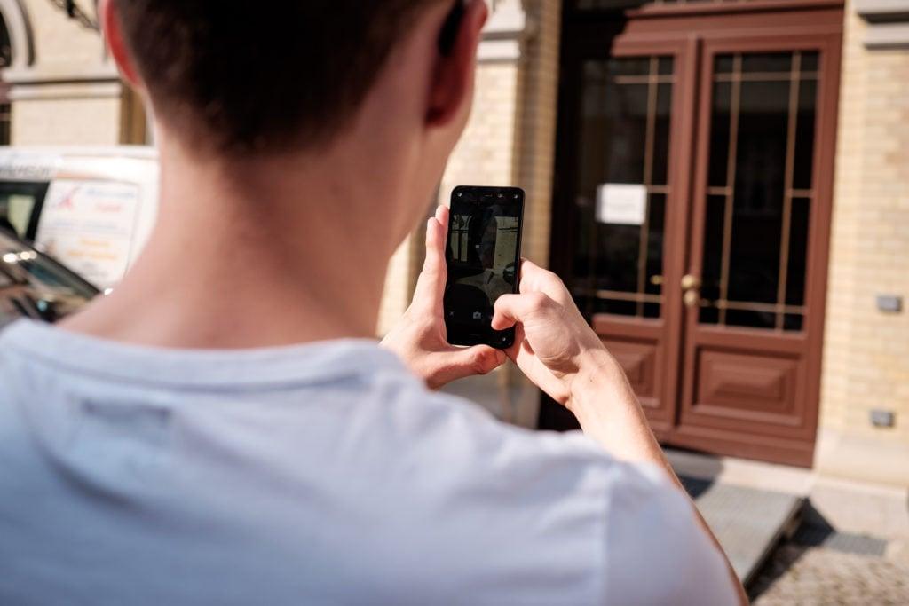 Eine Person macht mit ihrem Smartphone ein Bild von einer Tür und der Rampe davor