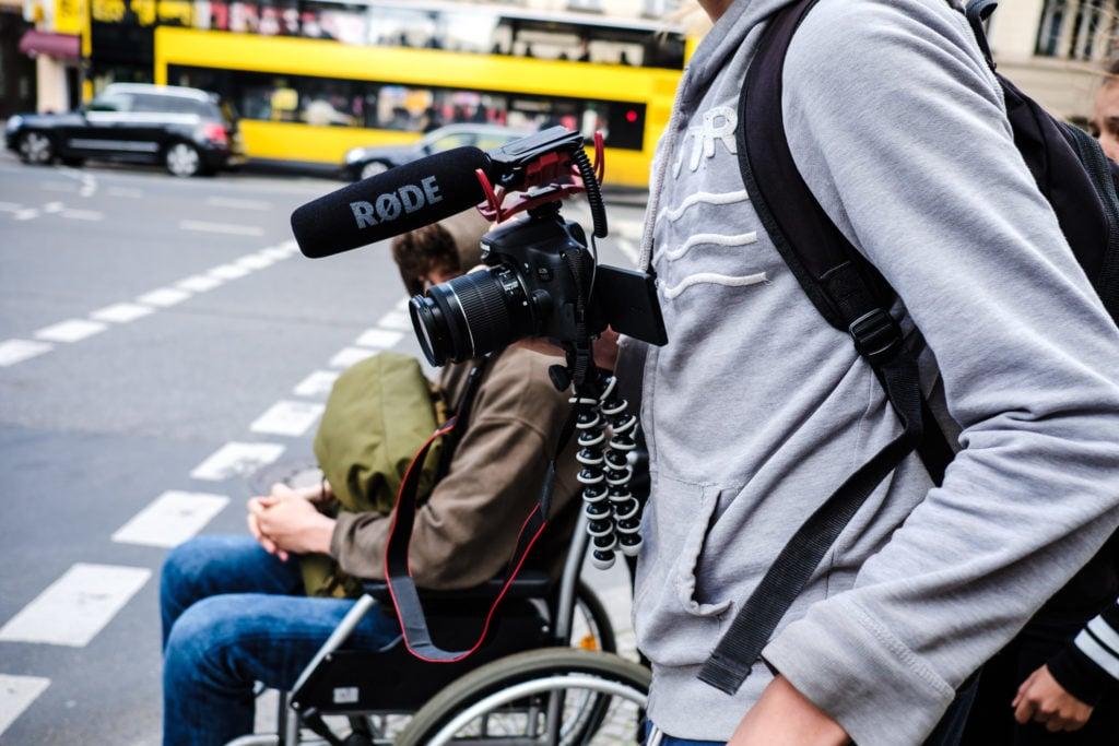 Eine Person mit Videokamera. Im Hintergrund eine Person im Rollstuhl