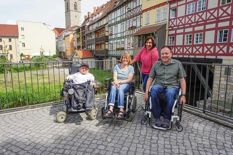 Vier Personen der Arbeitsgruppe , davon drei mit Rollstuhl in Erfurt vor den Fassaden der alten Fachwerkhäuser. Wheelmap-Botschafter Markus Walloschek befindet sich vorne links.