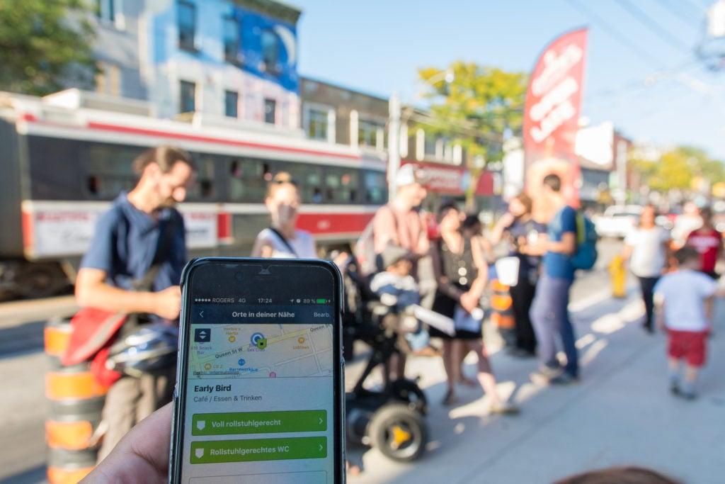 Smartphone-Bildschirm mit der Wheelmap-App. im Hintergrund steht eine Gruppe Menschen auf dem Gehweg.