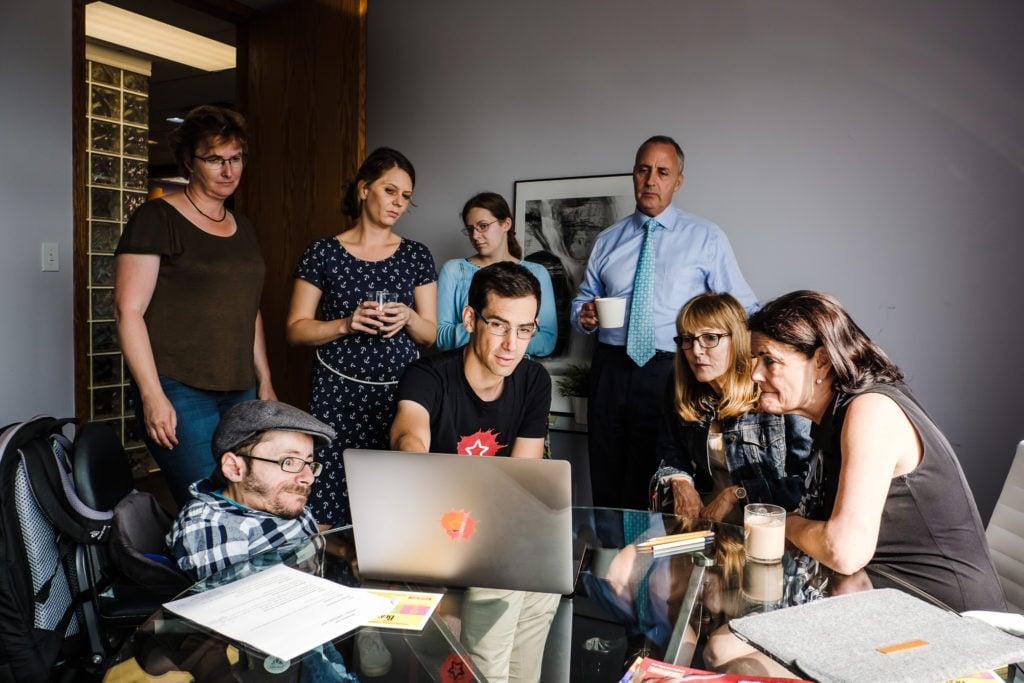 Mehrere Personen sitzen und stehen um einen Laptop der in einem Büro auf einem Tisch steht. Eine Person zeigt auf diesen Laptop und erklärt etwas