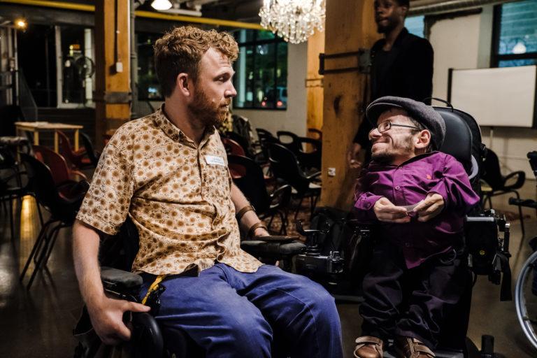 Raul Krauthausen im Rollsuhl mit einem anderen Rollstuhlfahrer unterhalten sich in einem leeren Event-Raum. Im Hintergrund stühle. Raul lächelt.