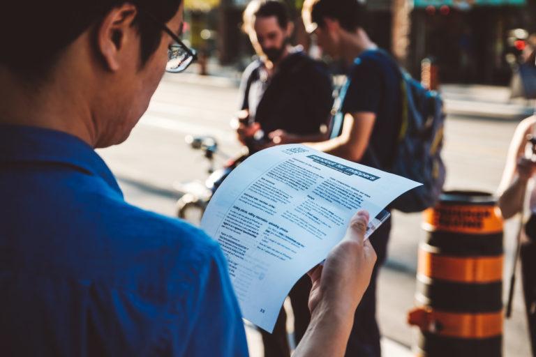 Ein Mann mit Brille schaut sich draußen die Hinweise auf dem Papier an.