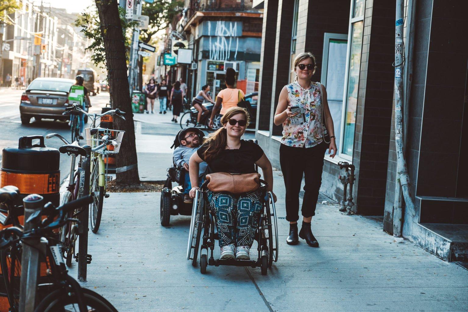 Zwei Rollstuhlfahrer*innen und eine Fußgängerin gehen die Straße entlang.