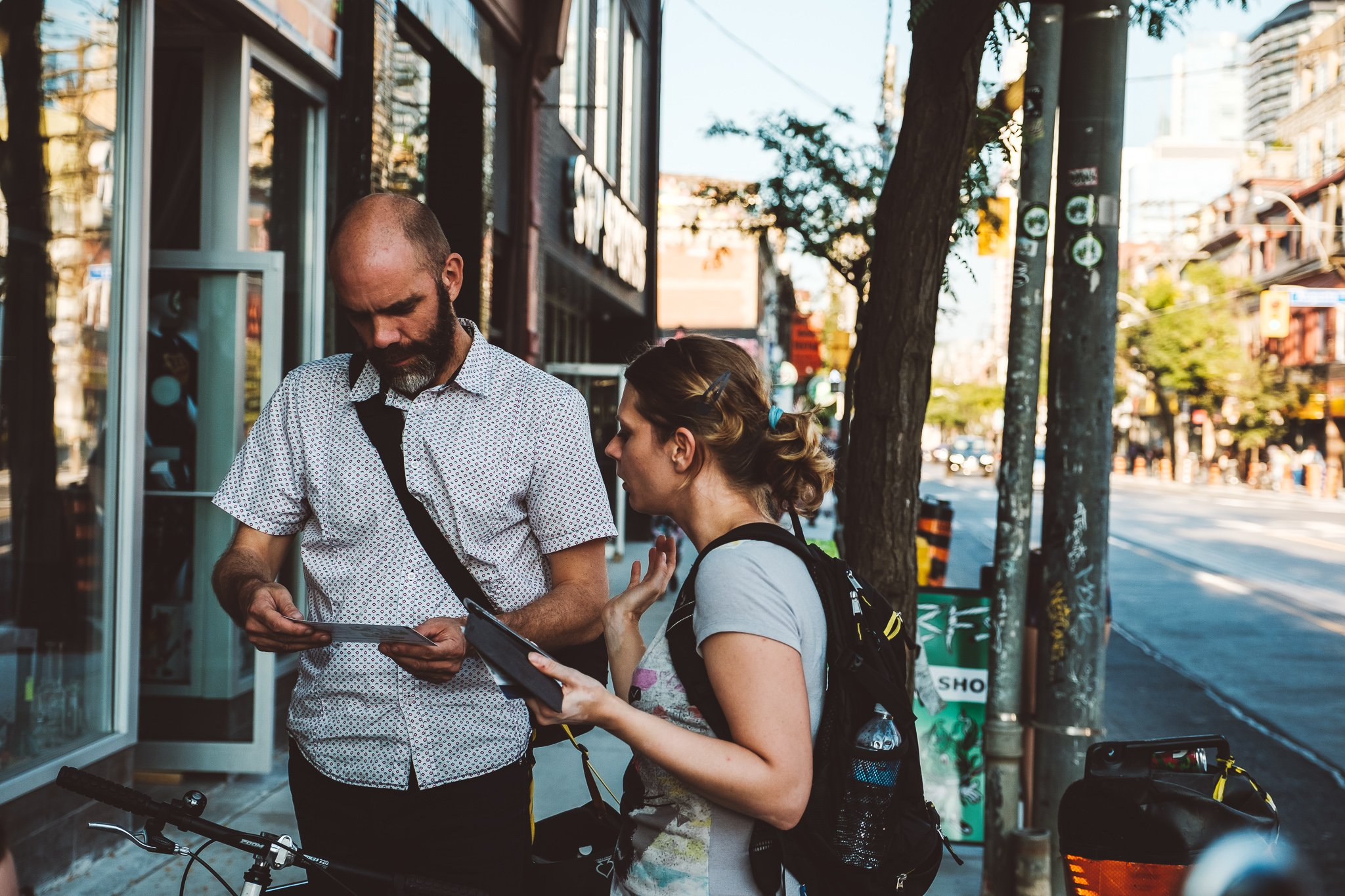 A Wheelmap ambassador talks to a passers-by on a sidewalk in Toronto and hands out a Wheelmap flyer.