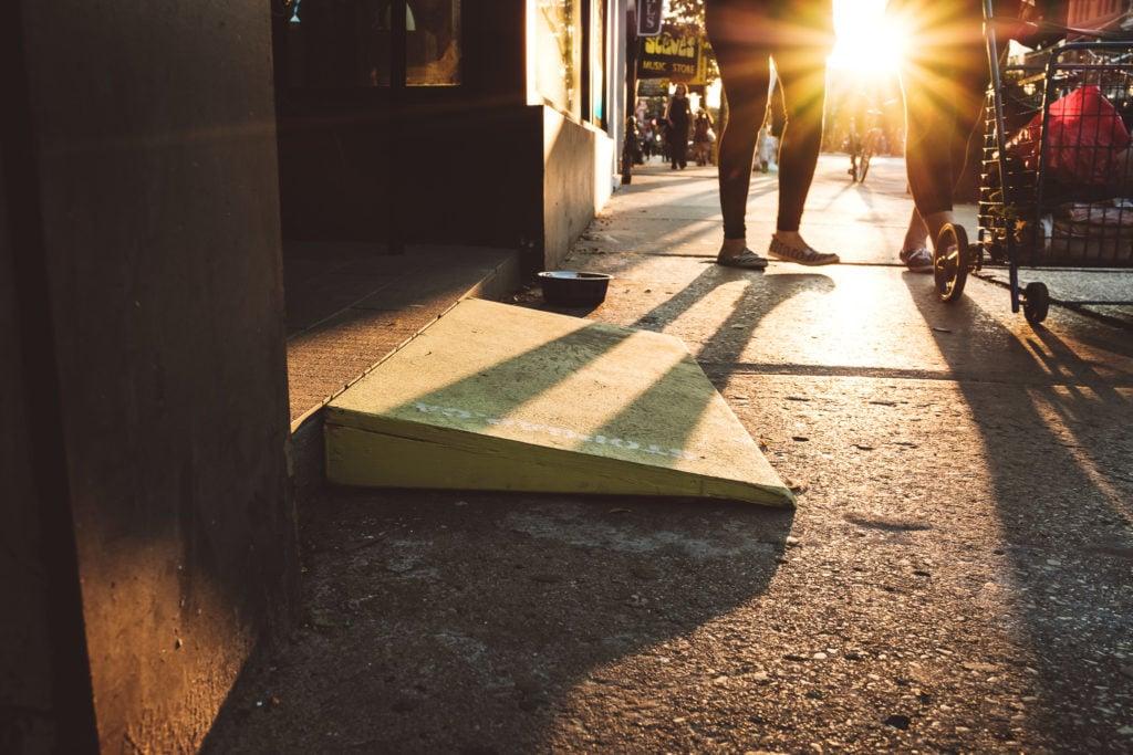 Eine kleine mobile Rampe überbrückt eine Stufe zum Bürgersteig. Im Hintergrund geht die Sonne unter und taucht alle in ein warmes Licht