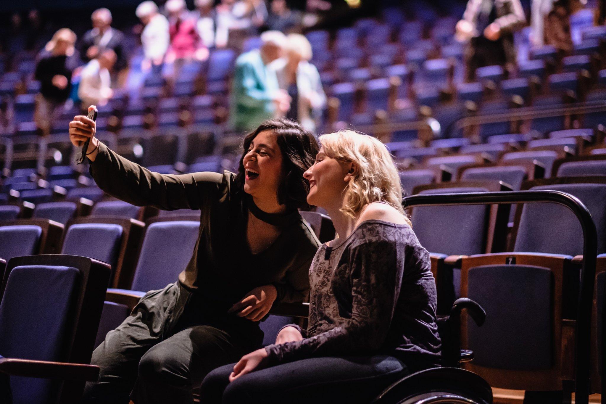 Zwei Frauen, davon eine mit Rollstuhl, sitzen in den Sesseln im Saal des Friedrichstadt Palastes . Sie wirken vergnügt und machen ein gemeinsames Selfie-Foto mit dem Smartphone während im Hintergrund weitere Besucher*innen ihre Plätze einnehmen.