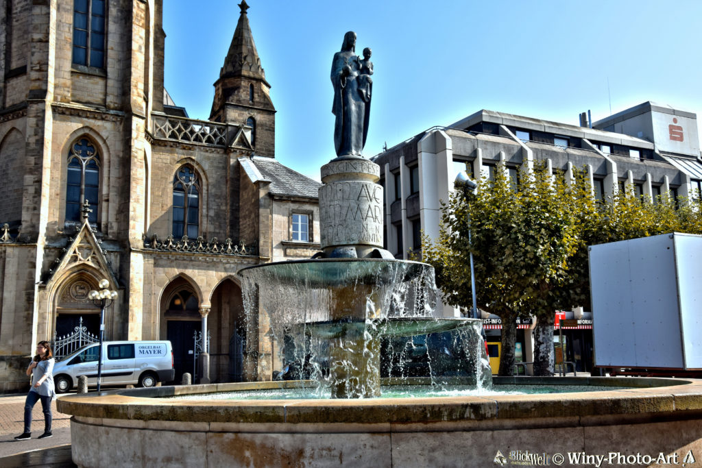 Im Vordergrund ist ein runder Brunnen mit einer Statue in der Mitte, hinten sieht man ein altes Gebäude. Es ist sonnig.