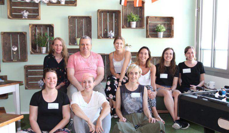 9 MitarbeiterInnen von Booking.com sitzen neben einem Tischkicker und haben Wheelmap.org Sticker auf der Brust.