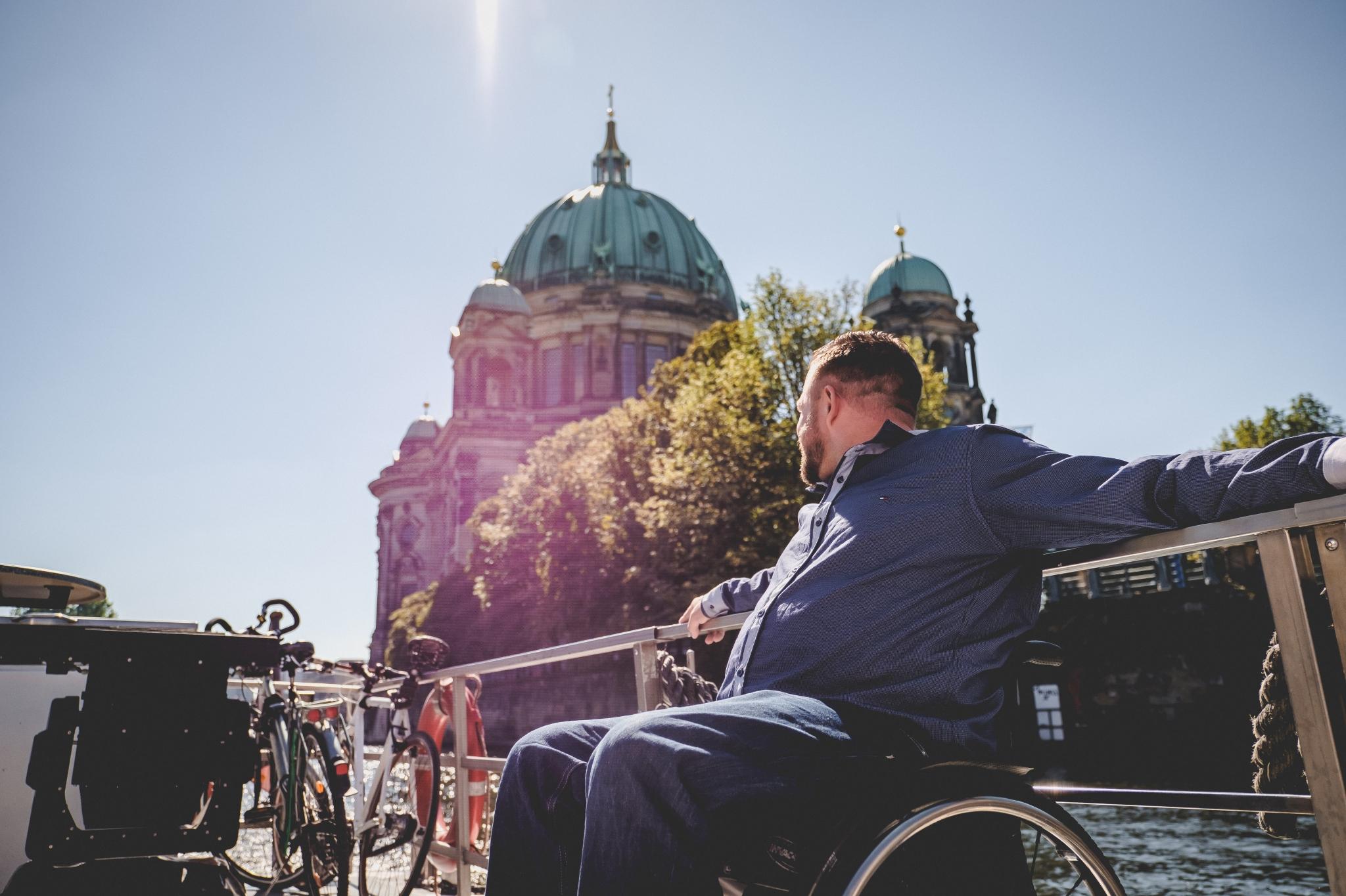 Ein Mann im Rollstuhl sitzt in der Sonne und schaut hinter sich über die Spree auf den Berliner Dom.