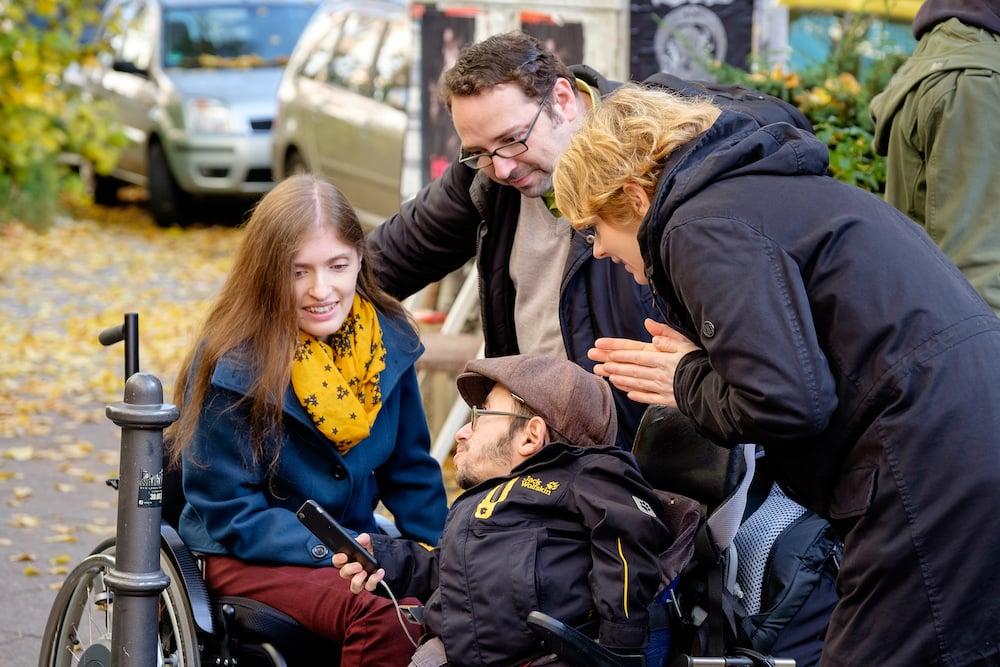 Zwei Personen im Rollstuhl, zwei Personen stehen dahinter. Alle schauen interessiert auf das Smartphone welches eine der Personen im Rollstuhl in der Hand hält.