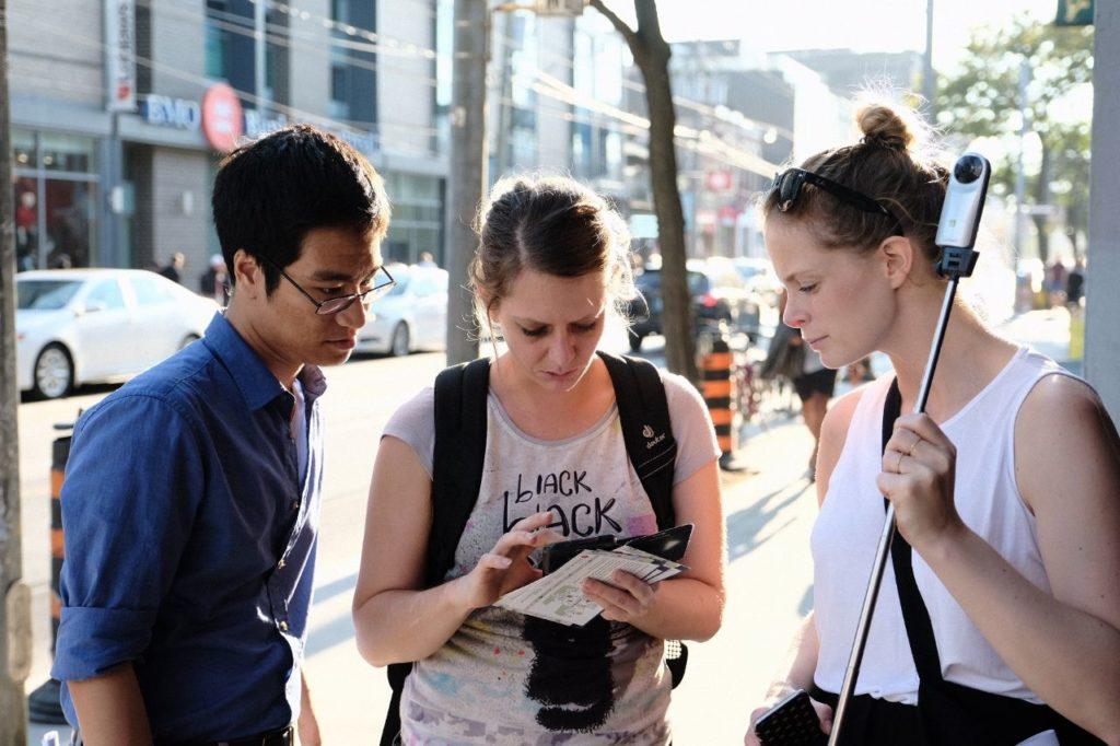 Drei Personen, die an einem Mapping Event teilenehmen. Sie schauen konzentriert gemeinsam auf ein Smartphone. Es ist sehr sommerlich und städtisch.