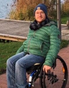 Ein Mann in Winterkleidung sitzt auf einem Rollstuhl und schaut freundlich in die Kamera. Im Hintergrund ist Gewässer und ein Steg.