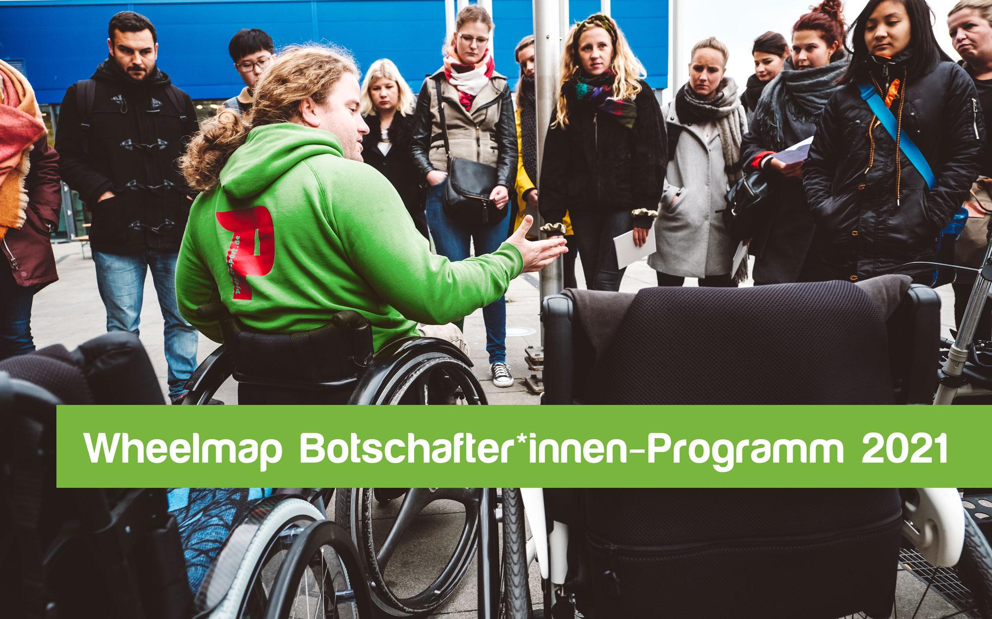 Ein junger Mann im Rollstuhl erklärt umstehenden Personen etwas. Text: Wheelmap Botschafter*innen-Programm 2021