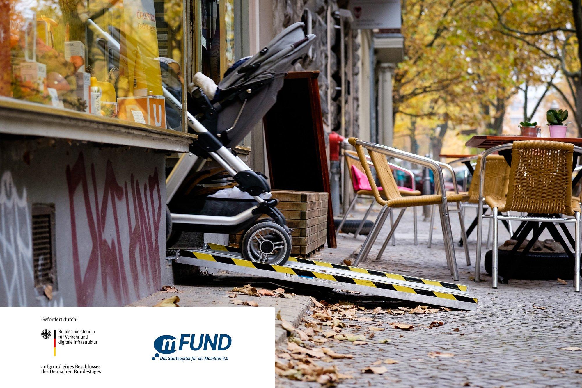 Ein Kinderwagen wird über eine Rampe aus einem Laden geschoben dazu das Logo vom mFund und Bundesministerium für Verkehr und digitale Infrastruktur (BMVI)