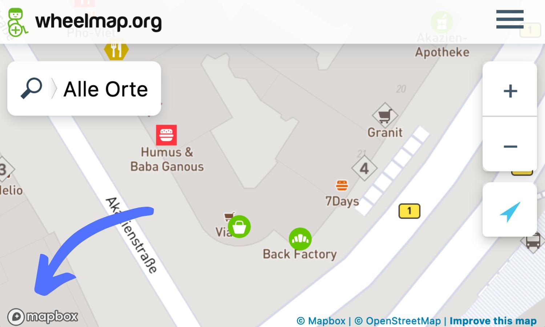 Screenshot der Wheelmap. Ein Pfeil zeigt auf das kleine Mapbox Logo unten links