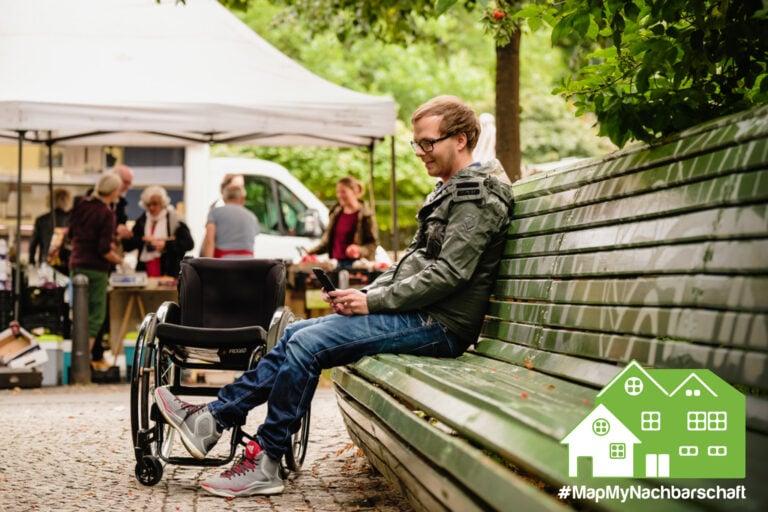 Ein junger Mann sitzt auf einer Parkbank und schaut auf sein Handy. Sein Rollstuhl steht neben der Bank