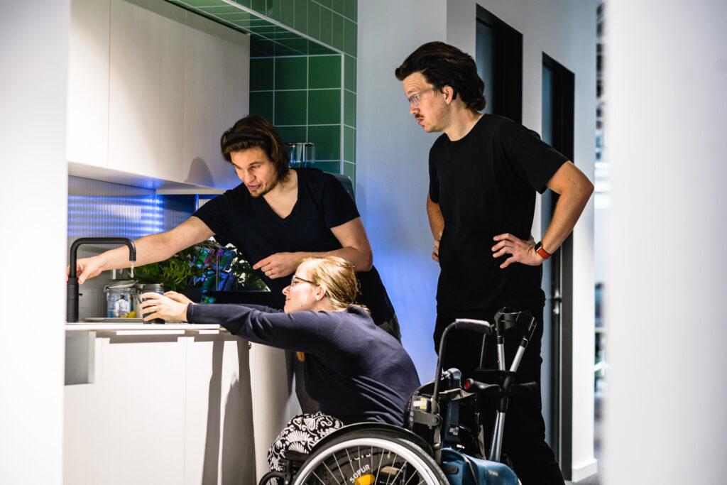Eine Person im Rollstuhl versucht an einen Wasserhahn in einer Teeküche zu kommen und schafft es nur mit großer Mühe. Zwei andere Personen helfen ihr und erkennen das Problem.