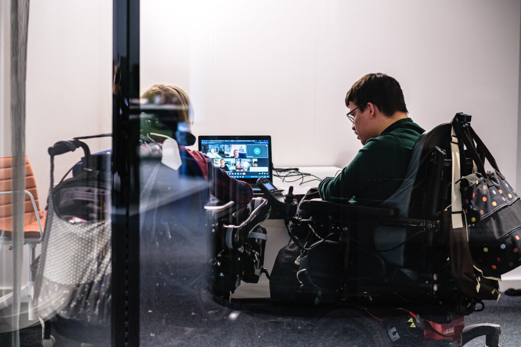 Zwei Menschen die einen Rollstuhl sitzen schauen zusammen auf einen Laptop