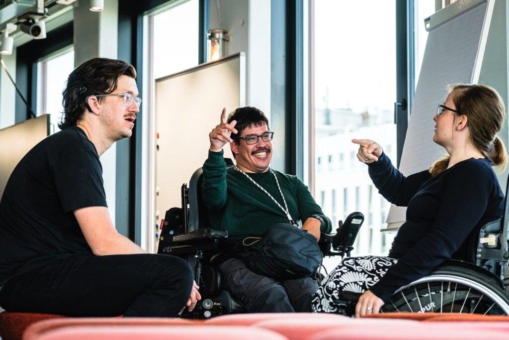 Drei Personen im angeregten Gespräch. Eine trägt eine Hörhilfe, zwei sitzen im Rollstuhl.