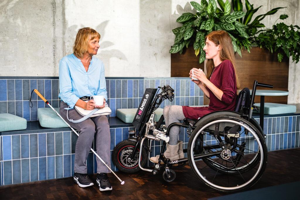 Zwei Personen trinken gemeinsam einen Kaffee. Der Langstock der linken Person lehnt an einer Bank. Die rechte Person nutzt einen Rollstuhl